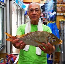 読谷海岸で45.2センチ、1.1キロのタマンを釣った山入端立美さん=9月23日