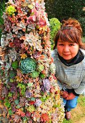 色鮮やかな多肉植物のツリーと銘苅清美さん=南城市玉城前川