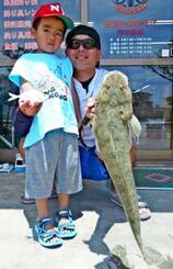 糸満釣り筏で57センチ、1・04キロのコチを釣った有銘良太さん(右)と秀馬さん=6月16日