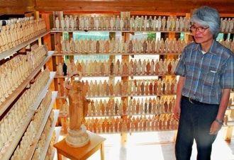 寄贈した1千体の仏像と製作した卯田明さん=4日、糸満市米須の私設美術館キャンプタルガニー