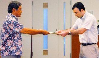抗議決議を田場議長(左)から手交されるスミス広報・報道部長=21日、北谷町役場