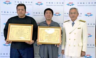 江口圭三部長(右)から感謝状を贈られた嶺井裕之さん(中央)と許田一文さん=21日、金武漁業協同組合