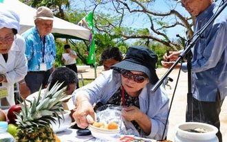 おきなわの塔に手作りのサーターアンダギーを供える平良正子さん=サイパン島