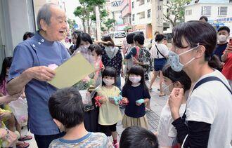 地域住民や子どもたちから花束や色紙を贈られ、笑顔を見せる宮城英雅院長(左)=30日、那覇市牧志