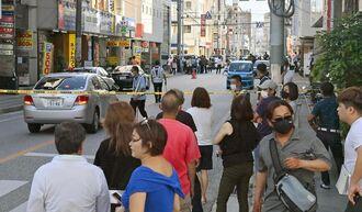 立てこもりとみられる通報で道路が封鎖され騒然となった現場周辺=14日午後5時半すぎ、那覇市若狭