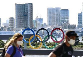 五輪マークのモニュメントの前を歩くマスク姿の人たち=21日午後、東京都港区