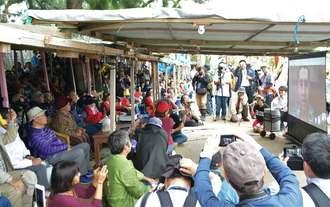 辺野古埋め立て作業の一時停止を求める請願活動を始めたロブ・カジワラさん(右手スクリーン内)の声に耳を傾ける市民=5日、名護市辺野古の米軍キャンプ・シュワブゲート前