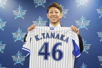 ユニホームを手にするDeNAの田中健=17日、横浜市の球団事務所(球団提供)
