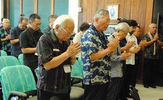 ハワイで亡くなり、遺骨が沖縄に戻っていない12人の御霊を鎮めようと合掌する参列者。左手前から慰霊祭実行委員会の渡口彦信共同代表、高山朝光共同代表ら=4日、ハワイ州ホノルル市・慈光園本願寺