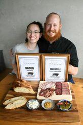 大会の賞状と出品作を前に喜ぶトーマス・エヴンさん(右)と娘のエイジィアさん=3月30日、沖縄市・ベーコンバージャパン