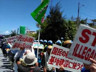 プラカードを掲げて埋め立てに抗議する市民ら=12日午後0時40分ごろ、名護市辺野古