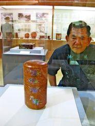 コレクション展で、琉球王朝時代とされる漆器を眺める翁長さん=4日、那覇市・パレットくもじ4階の市歴史博物館