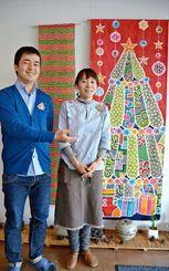 クリスマス仕立ての作品を作ったデザイナーのEYELANDさん(右)とスタッフの山城信吾さん=22日、浦添市前田の城紅型染工房