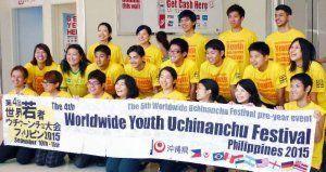 フィリピンに向けた出発式で、世界若者ウチナーンチュ大会の横断幕を持って記念撮影する参加者ら=9日、那覇空港(県広報交流課提供)
