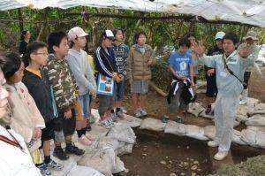 市の担当者から貝が集積する発掘場所の説明を聞く野底小の子どもたち=石垣市野底