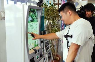 券売機で入島料を支払う男性=1日、石垣市美崎町の石垣港離島ターミナル