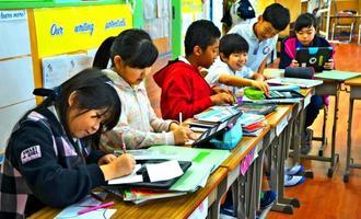 iPadを活用しながら、とり年にちなんだ年賀状を作る子どもたち=那覇市楚辺・オキナワインターナショナルスクール