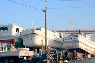 泊漁港の敷地内に積み上げられた放置艇。老朽化が進んでいる船もある=那覇市港町の泊漁港