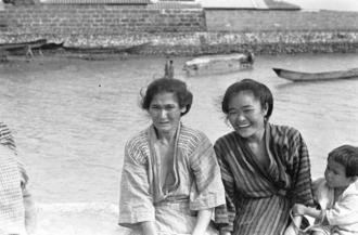 1935年撮影時の説明に「糸満で、漁から帰る夫を待つ1枚」とある1枚。中央右隣りの若い女性について、上原啓子さん(84)ら複数の人が「ミスー(ミチュー)バーチー」と通称を覚えている。バーチーは「おばさん」ほどの意味。取材では本名は判明していない。現在の糸満市糸満、前端区辺りと見られる。띱 西島本和江さん(81)は戦後、20代半ばのころ、この人が「姓は上原だったと思うが、50代くらいで、もっとふっくらしていた時」に雑貨や果物を売っていた前端区の店を訪れた。「店は娘が継いだが道路拡幅のため今から7、8年前に立ち退いた」と語る
