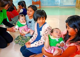生後10カ月の双子の女の子を抱く小学3年生の児童たち=26日、那覇市立若狭小