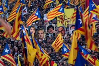 16日、スペイン・バルセロナで、独立派政治家の写真を掲げて裁判に抗議するデモ参会者ら(AP=共同)