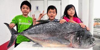 城間正永さんは1日、伊平屋島の野甫港の先端付近で120センチ、24キロのロウニンアジを釣った。写真は次女の杏鈴ちゃん(右)と長男の永君(中央)ら