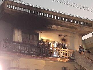 消火作業に取り組む消防隊員ら=12日午後6時20分頃、沖縄市安慶田