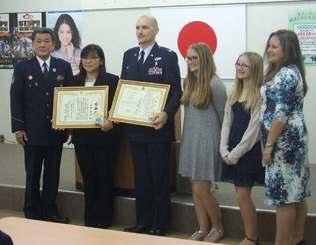 人命救助で感謝状を受けたジョン・コットンさん(左から3人目)と金城菜未さん(同2人目)=24日、嘉手納署
