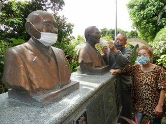 父(手前)と祖父の胸像にマスクを掛ける嵩本さん夫妻=3月、石垣市新川