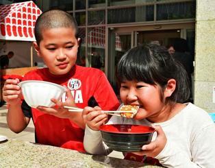 「サクサクでおいしいね」。お昼時、きょうだいでマグロカツをぱくり=21日、那覇市久茂地・タイムスビル