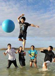 ビーチでは、中学生が水につかり大きなボールでバレーを楽しんでいた=29日午後、宜野湾市・トロピカルビーチ