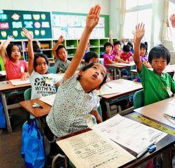 夏休みの宿題の説明を聞き、返事をする子どもたち=18日、那覇市・真嘉比小学校(金城健太撮影)