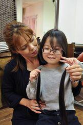 ばっさり切った髪を手にする長浜妃桜等ちゃん(右)と母親の恵里奈さん=27日、那覇市国場の美容室「quaint」
