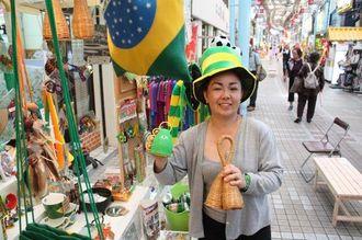 ブラジル雑貨店の前で、W杯の公認応援楽器「カシローラ」を右手で振る翁長巳酉さん。サンバの打楽器奏者でもある=10日、那覇市の平和通り