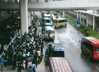 レンタカーの送迎バスを待って行列をつくる観光客ら=那覇空港国内線ビル前(資料写真、県レンタカー協会提供)