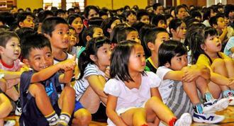 食い入るようにMASAさんのマジックを見つめる子どもたち=25日、名護小学校