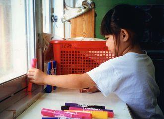 5歳当時の新城千奈。マジックペンを並べている。この頃からよく絵を描いていたという(提供)