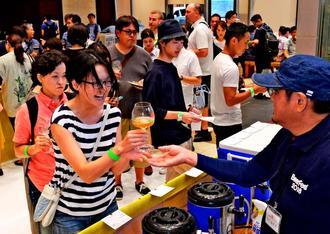 県内外の銘柄を飲み比べ、それぞれのテイストを楽しむ来場者=27日、那覇市久茂地・タイムスビル