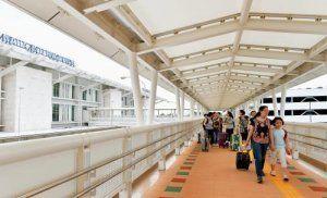 国内線旅客ターミナルと国際線旅客ターミナルを結ぶ立体連絡通路を利用する観光客=15日午後、那覇空港