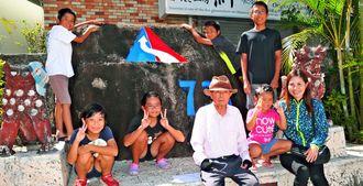 交通安全を願い「730記念碑」のペンキを塗り直した宮良永重さん(前列中央)と孫ら=石垣市美崎町