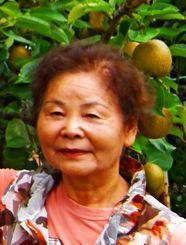(下)梨の木の前で笑顔を見せる米須スミさん
