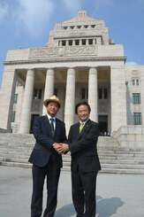 国会に初めて登院し、伊波洋一参院議員(右)と握手する高良鉄美参院議員=1日午前、国会