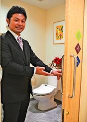 LGBTに配慮したトイレを作ったホテルパームロイヤルNAHAの高倉直久総支配人。緑を基調としたマークが表示されている=2日、那覇市の同ホテル
