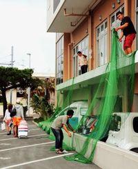 観光客が行き交う中、防護ネットを張る作業を続けるホテル従業員ら=26日午後、宮古島市平良西里