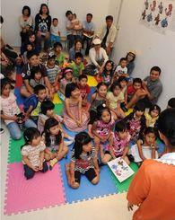 絵本の読み聞かせに夢中になる子どもたち=5日午前、那覇市おもろまちの県立博物館・美術館