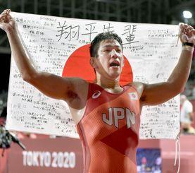 男子グレコローマン77キロ級で銅メダルを獲得し、メッセージが書かれた日の丸を掲げる屋比久翔平=幕張メッセ