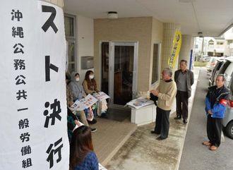 ストライキで会社の前に座り込む従業員ら=14日午前、宜野湾市内