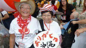 国際通りのパレードで笑顔のマーリンさん(左)と米国オハイオ州から来沖した妹のフェイさん=2001年、那覇市・壺屋小学校