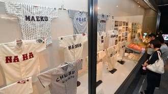 沖縄の高校野球の歴史を振り返る展示に見入る来館者=5日、那覇市の県立博物館・美術館