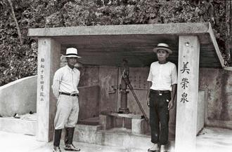 1935年4月に改築されたばかりの「美栄泉(ミーガー)」と知念賢榮さん(右)。一緒に写っているのは美東尋常高等小学校の宮里信栄教諭。戦後、同校の校長も務めた。ミーガーは野菜を洗ったり、洗濯をしたりする場所だった。比屋根朝栄さんによると、知念さんの指示でコンクリートを使って改築したという。県生コンクリート工業組合の仲田康司専務理事は「当時、沖縄ではコンクリートは製造されておらず、県外から資材を運んでおり、高価なものだった。経済力がある集落だったことがうかがえる」と話した(写真は朝日新聞社提供)